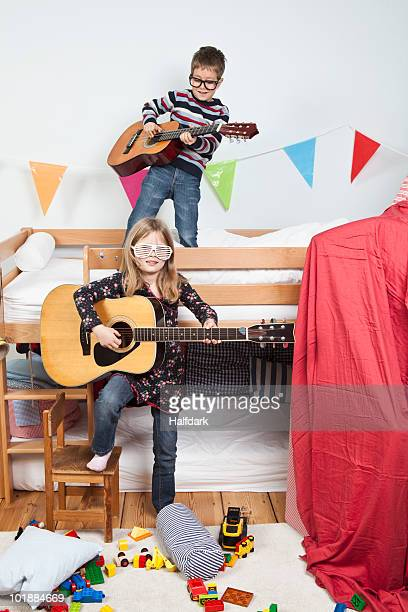 Two children playing with guitars in a child's playroom