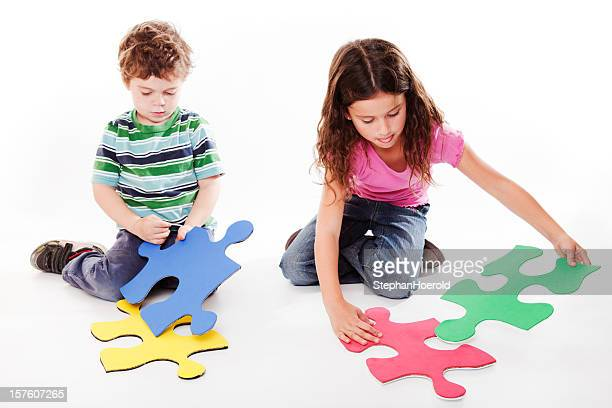 Two children playing with huge puzzle pieces, isolated on white