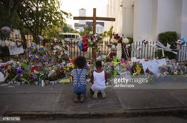 Two children pray near thousands of flowers and cards left in condolence outside Emanuel AME Church in Charleston South Carolina on June 23 2015...
