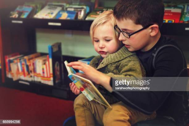 two children reading books in a library