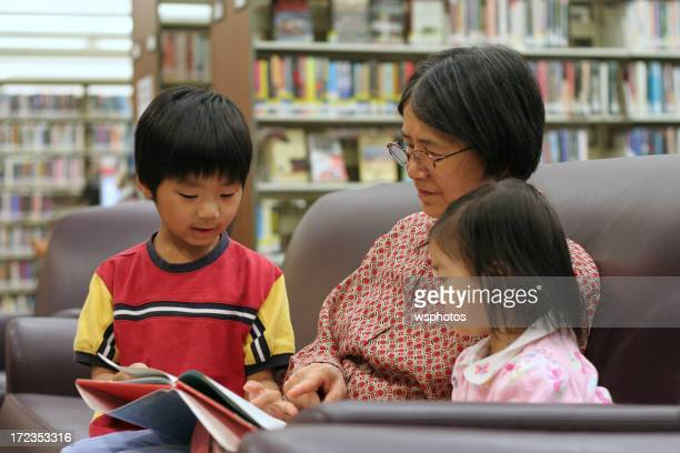 Two children reading with their grandmother in a library