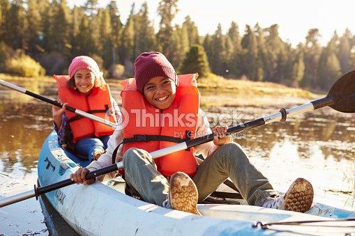 Two Children Rowing Kayak On Lake : Stock Photo