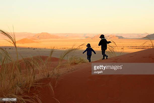 Two Children Running Down The Sand Dunes in Sossusvlei Namibia