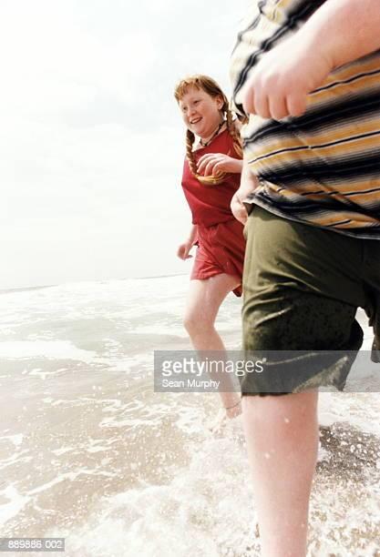 Two children (10-13) running in ocean shallows