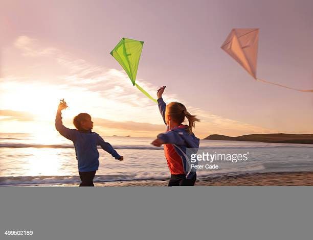 Two children running on beach with kites at sunset