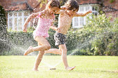 Two Children Running Through Garden Sprinkler