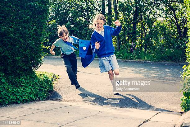 Two children running to home from school.