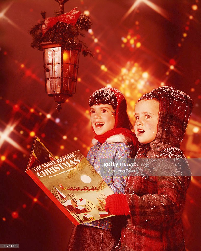Two children singing Christmas carols. : Stock Photo