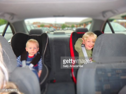 Two children sitting in back of car