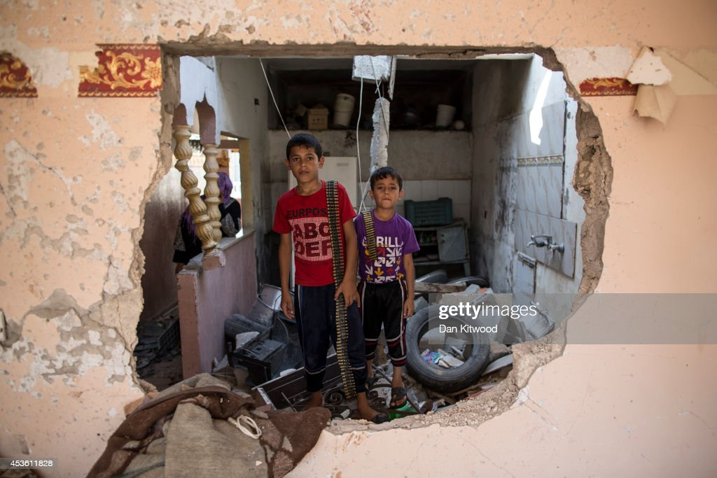 Two children stand in their demolished home holding ammunition on August 14, 2014 in Beit Hanoun, Gaza. A new five-day ceasefire between Palestinian factions and Israel went into effect today as part of efforts aimed at reaching a permanent truce deal. The Palestinian death toll from Israel's weeks-long military onslaught on the Gaza Strip has risen to 1959, according to a Palestinian Health Ministry spokesman.