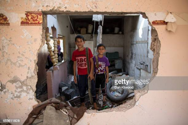 Two children stand in their demolished home holding ammunition on August 14 2014 in Beit Hanoun Gaza A new fiveday ceasefire between Palestinian...