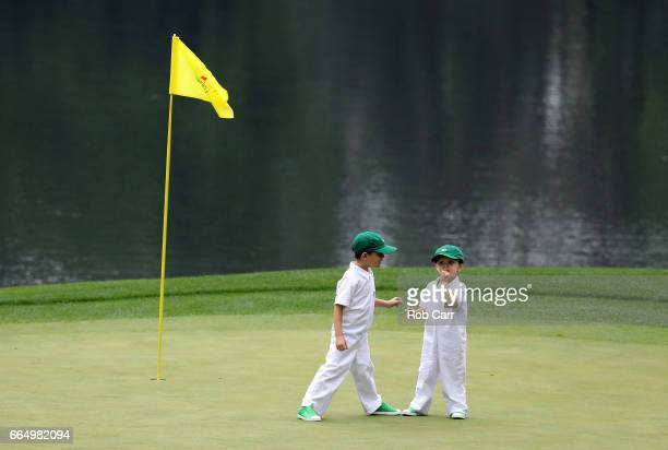 Two children stand on a green during the Par 3 Contest prior to the start of the 2017 Masters Tournament at Augusta National Golf Club on April 5...
