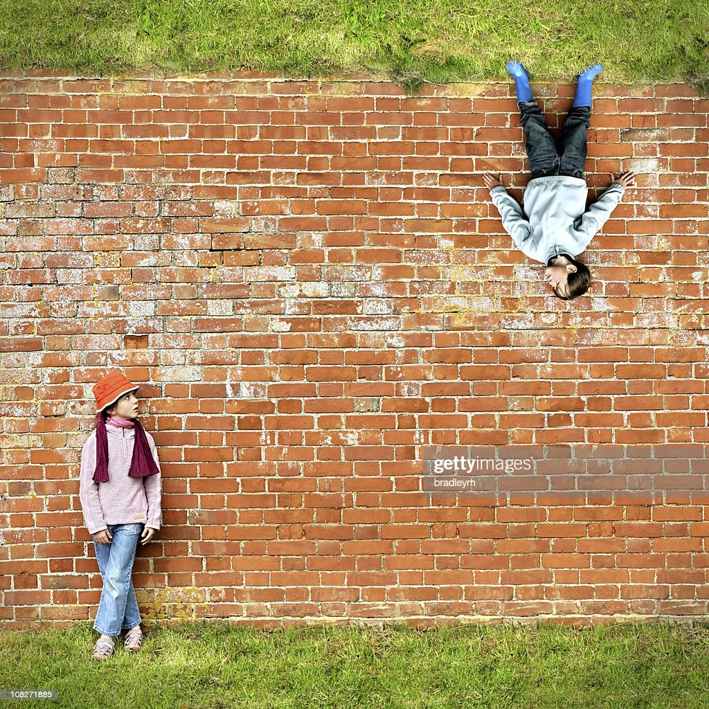 Two Children Standing Against Brick Wall : Stock Photo
