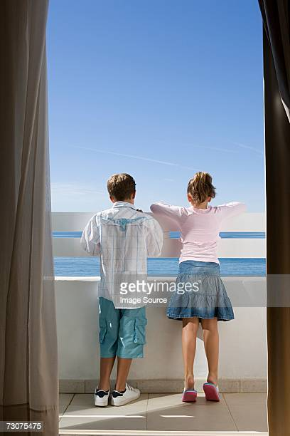 Two children standing on a balcony