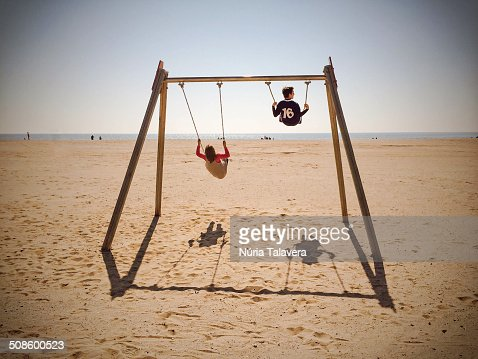 Two children swinging on the beach : Stock Photo