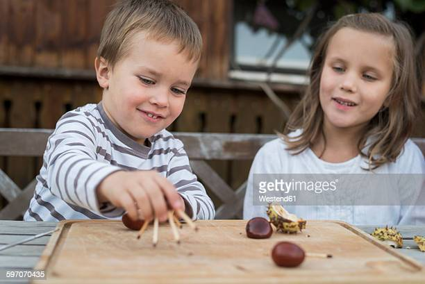 Two children tinkering with chestnuts