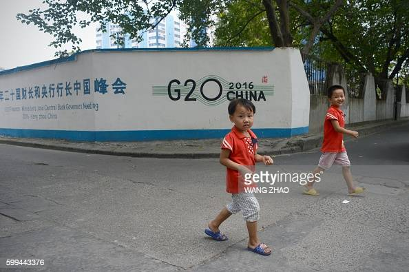 Two children walk past a wall painted painted with the 11th G20 Leaders Summit logo at a residential area in Hangzhou the host city for the summit on...