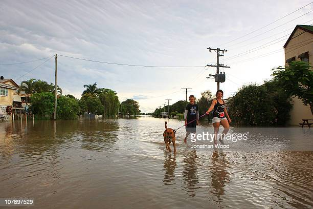 Two children walk their dog through a flooded street on January 6 2011 in Rockhampton Australia Floodwaters peaked at 92 metres yesterday in the...