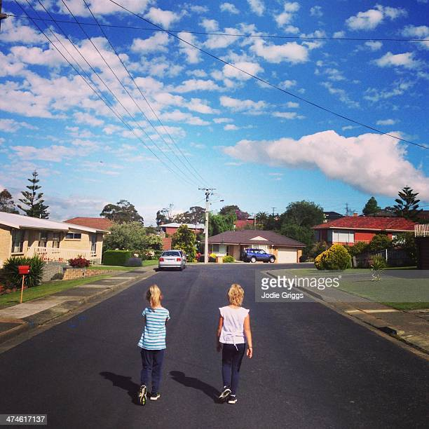 Two children walking down suburban street