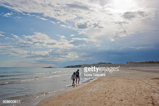 Two children walking on the beach : Stock Photo
