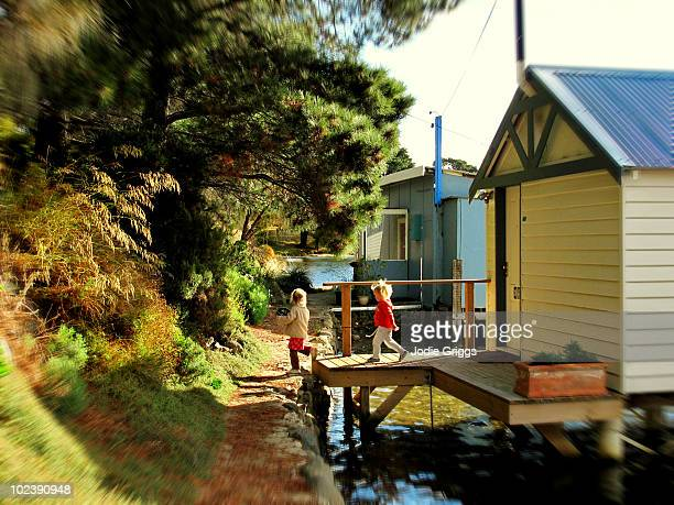 Two Children walking past Boat Houses