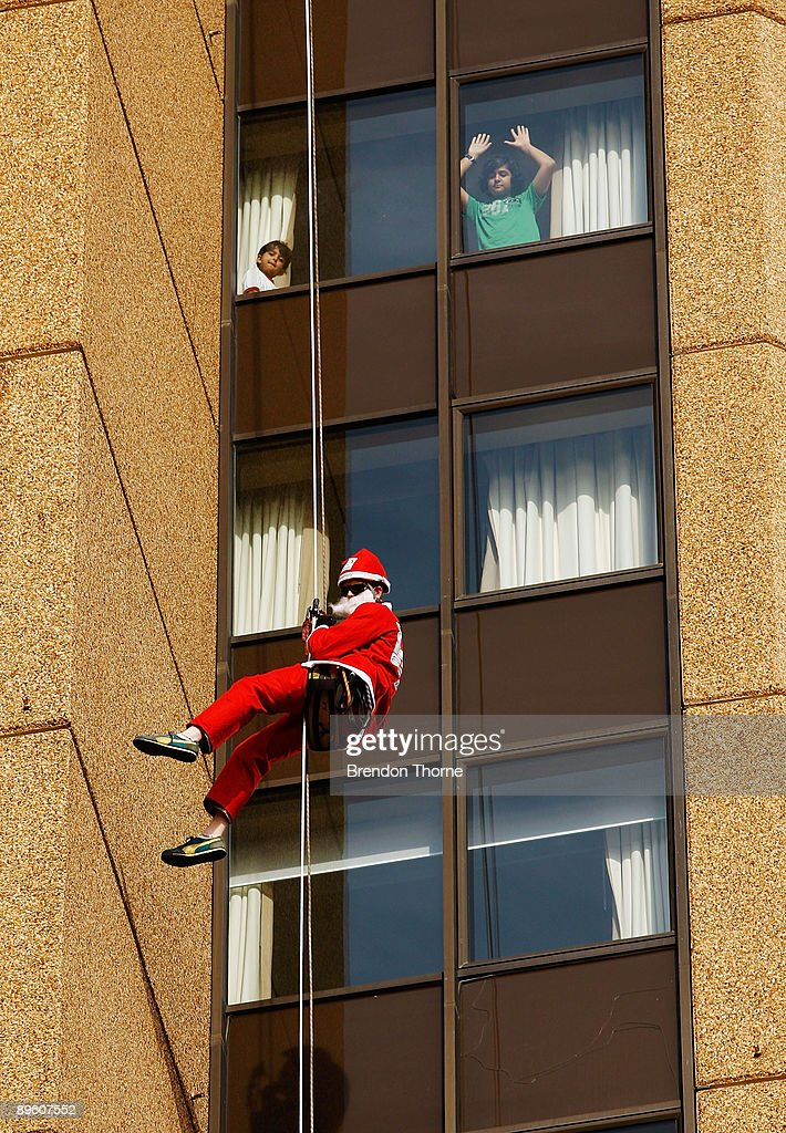 Two children watch from a hotel room as a Santa abseils down the front of Sydney's Four Season's Hotel to launch the Sydney Santa Fun Run on August 5, 2009 in Sydney, Australia. The children's charity Variety are hosting the event on November 29 for which they hope to encourage 5000 Sydney-siders to wear a Santa suit and raise funds for disadvantaged children.