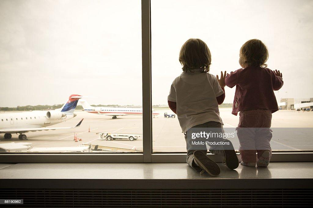 Two Children Watch Planes Land : Stock Photo