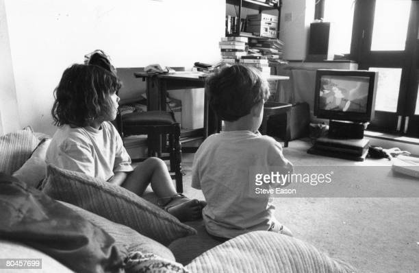 Two children watching a 'Tom And Jerry' cartoon on television August 1995