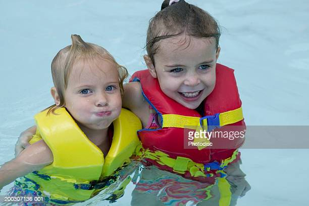 Two children (4-5), (6-7), wearing life jackets in swimming pool, portrait