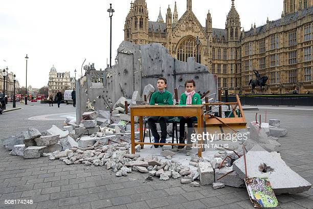 Two children whose school was bombed in Aleppo pose in a mockup meant to symbolise a destroyed classroom set up by charity Save the Children outside...