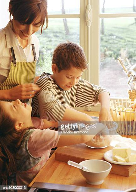 Two children with hands in bowl, woman smiling