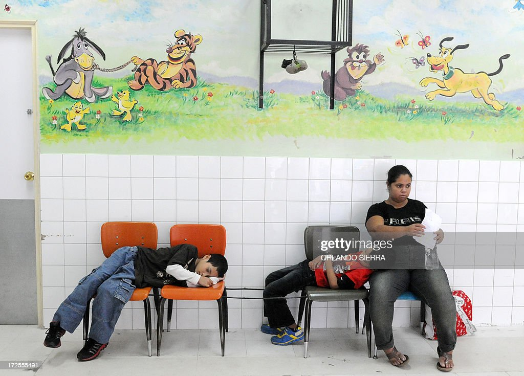Two children with symptoms of dengue fever await to be seen at Hospital Materno Infantil medical centre in Tegucigalpa on July 3, 2013. The disease vectored by the Aedes aegypti mosquito has killed ten people in Honduras so far this year. AFP PHOTO /Orlando SIERRA.