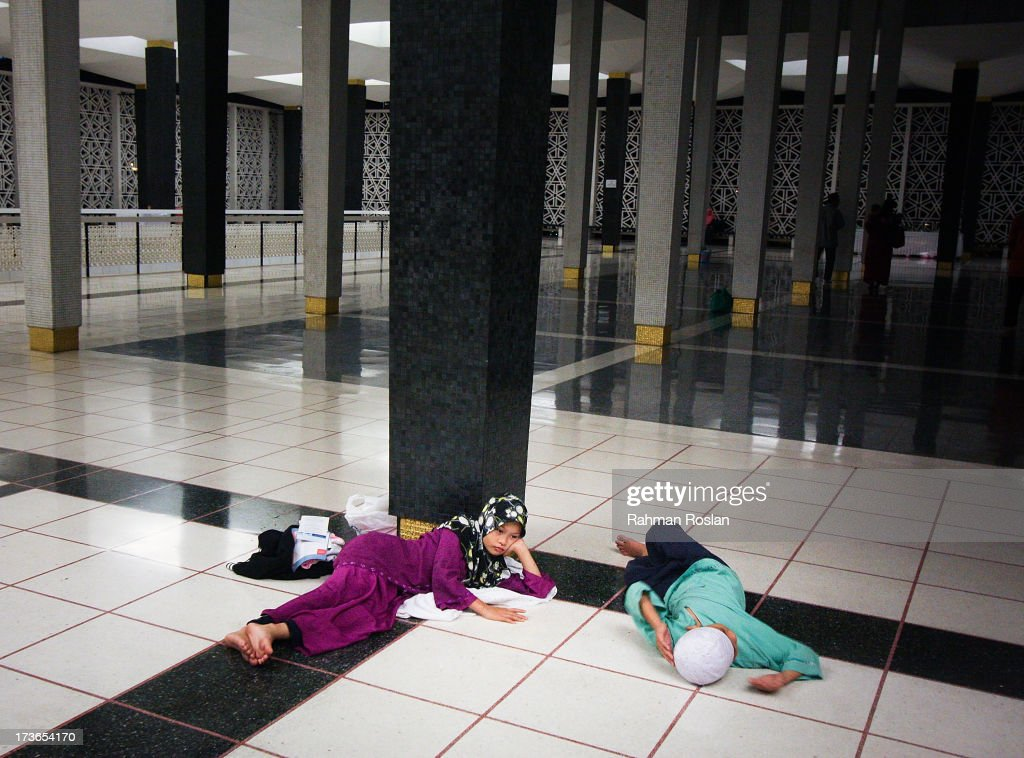 Two childrens wait for their mother to finish her night prayer known as Tarawikh as millions of Muslims observe the holiday of Ramadhan on July 16, 2013 in Kuala Lumpur, Malaysia. During Ramadhan, Muslims refrain from consuming food, drinking liquids, smoking, swearing, and engaging in sexual relations from dawn till sunset.