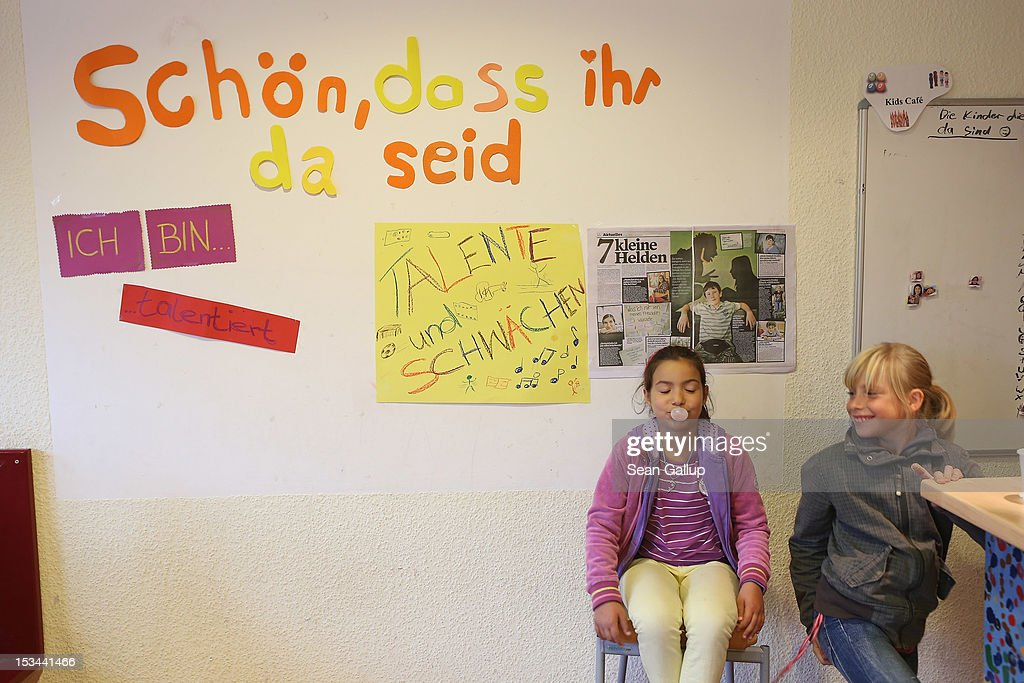 Two childrensit next to a pin-up wall with a headline that reads: 'It's nice that you're here' at the 'Arche' youth center in Marzahn-Hellersdorf district on October 5, 2012 in Berlin, Germany. The Arche (which means Ark) is a Christian-based facility that provides children of all ages with a hot lunch, help with homework, arts and play facilities and in general a welcome place to come to in Marzahn-Hellersdorf district in east Berlin, a district with high levels of unemployment and social problems. An employee said up to 90% of the children come from challenged families and that many arrive at Arche illiterate.