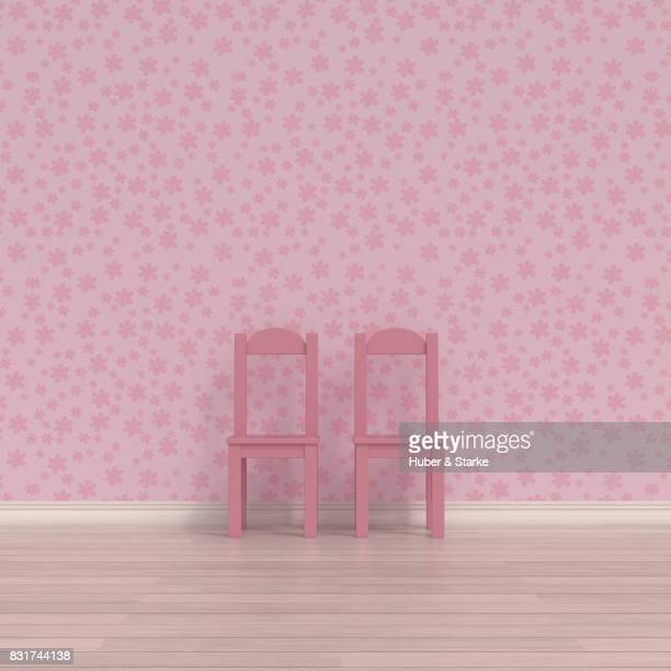 Two child's chairs in front of floral patterned wall paper