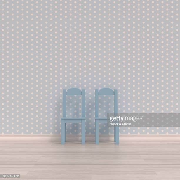 Two child's chairs in front of spotted wall paper
