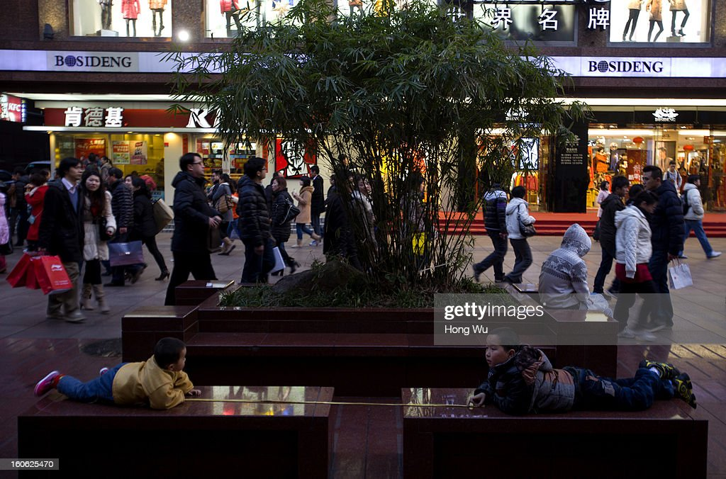 Two Chinese boys play games in Nanjing Road Walking Street on February 3, 2013 in Shanghai, China.