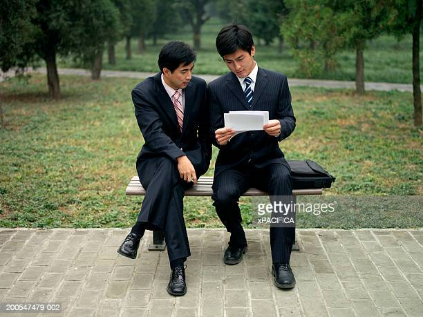 Two Chinese businessmen reading documents on bench in park