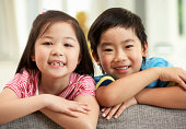Two Chinese Children Relaxing On Sofa At Home Smiling To Camera
