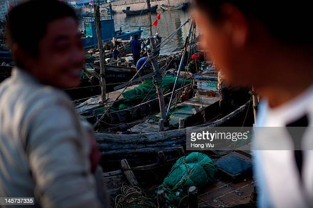 Two Chinese fishermen chat at a port on May 21 2012 in Qingdao China Marine fishery resources in China becomes less and lees due to excessive fishing...