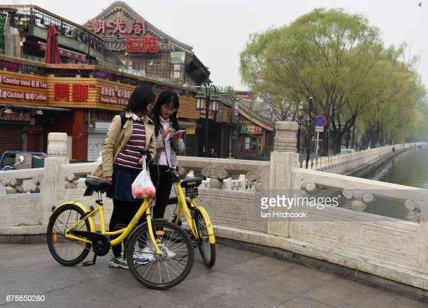 Two Chinese girls are seen looking at a smart phone with their 'ofo' bikes on a bridge on April 4 2017 in Beijing China
