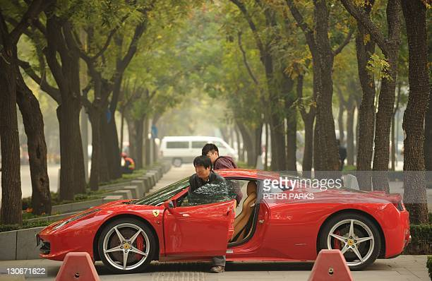 Two Chinese men get into a new Ferrari 458 Italia in Beijing on October 28 2011 The head of the European bailout fund dampened hopes October 28 that...