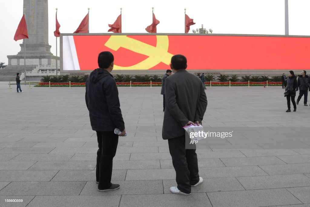 Two Chinese men look at a sign of Communist Party of China displayed on a electronic board at Tiananmen square during the 18th National Congress of...