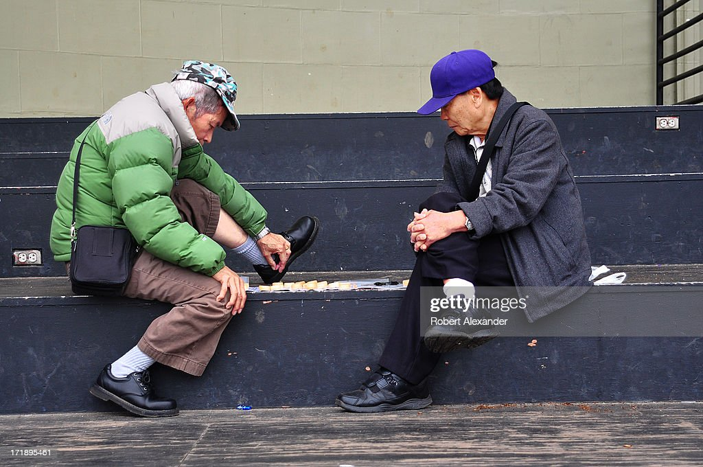 Two Chinese men play a game of Chinese chess at Spreckels Temple of Music, also known as 'the Bandshell', in San Francisco's Golden Gate Park.