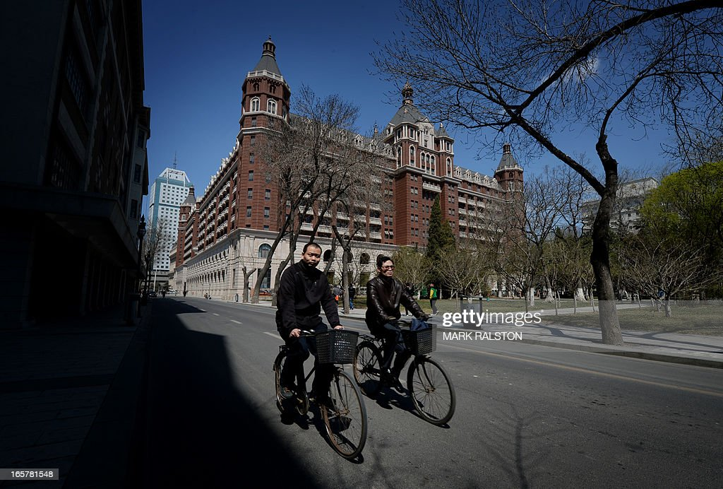 Two Chinese men rides their bikes past a recently renovated historic building in the foreign concession area of Tianjin on April 6, 2013. The city has almost completed a program of restoring its foreign buildings to their former condition. AFP PHOTO/Mark RALSTON