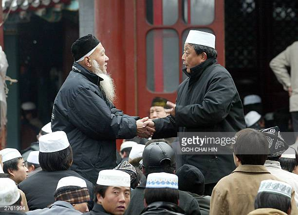 Two Chinese Muslims greet each prior to Eid alFitr prayers at the Niujie mosque in Beijing 26 November 2003 China's 20 million Muslims joined the...