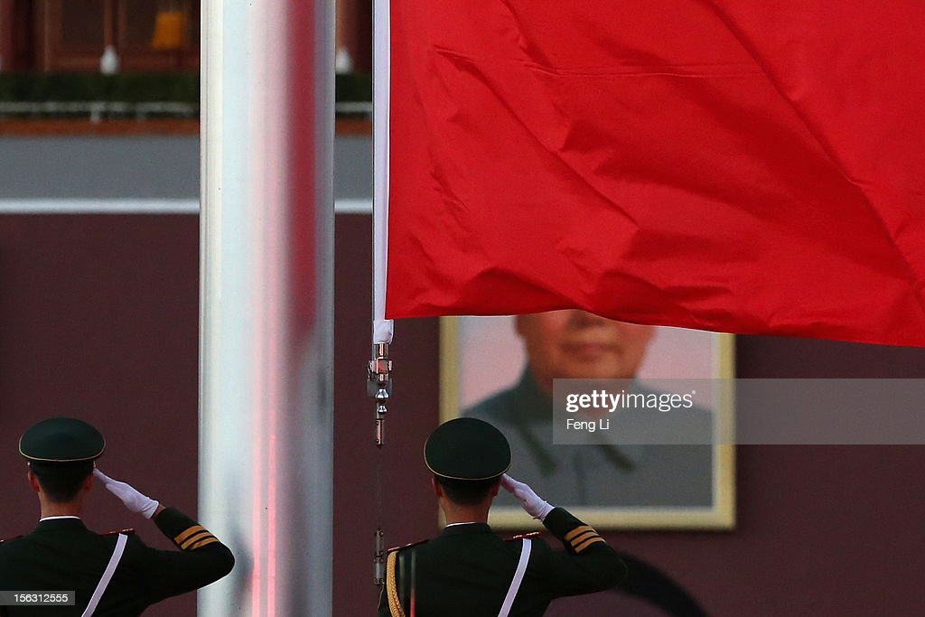 Two Chinese paramilitary police officers salute during the flag-lowering ceremony in front of a giant portrait of the late chairman Mao Zedong at Beijing's Tiananmen Square on November 13, 2012 in Beijing, China. The 18th National Congress of the Communist Party of China (CPC) will close Wednesday morning after electing members and alternate members of a new CPC Central Committee and members of a new Central Commission for Discipline Inspection.