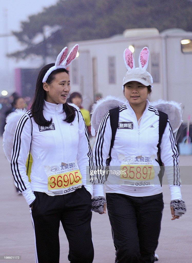 Two Chinese participants wearing rabbit ears head to the starting line before the start of the Beijing Marathon in the Chinese capital on November 25, 2012. A total of 30,000 runners took part in the race.