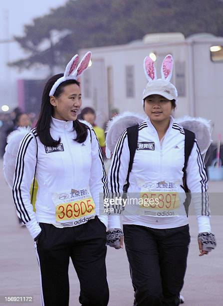 Two Chinese participants wearing rabbit ears head to the starting line before the start of the Beijing Marathon in the Chinese capital on November 25...
