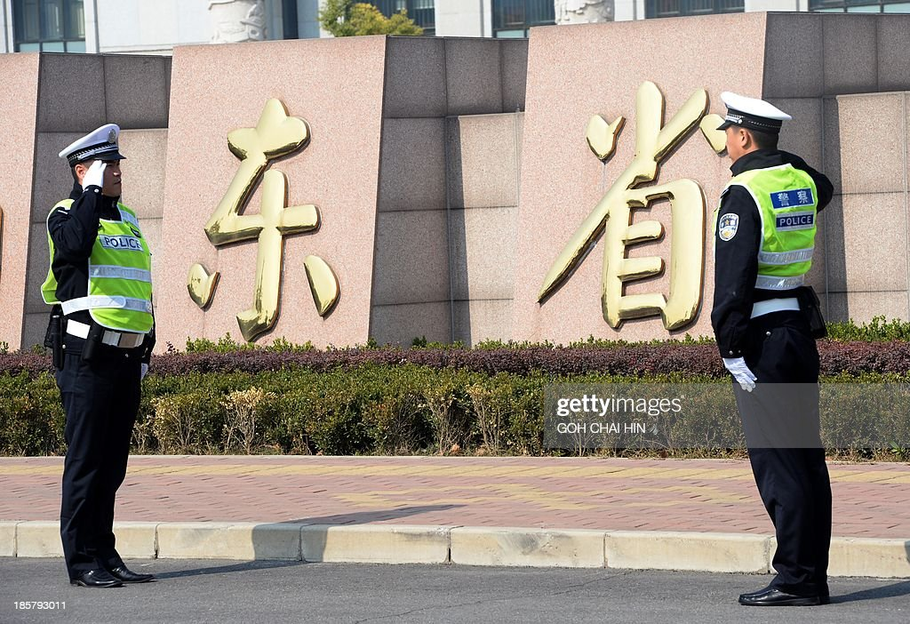 Two Chinese police officers salute each other outside the Shandong high court building in Jinan, east China Shandong province on October 25, 2013. A Chinese court rejected fallen politician Bo Xilai's appeal against his corruption conviction and confirmed his life sentence on October 25, as authorities looked to draw a line under a damaging scandal. AFP PHOTO/GOH CHAI HIN